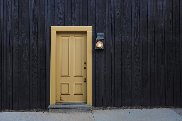 žluté dveře, lampička, tmavá stěna