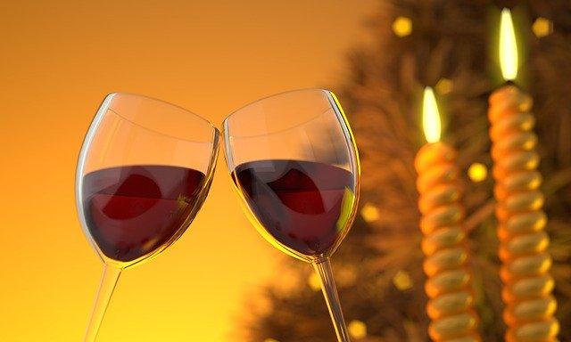 dvě sklenky s červeným vínem nakloněné k přípitku